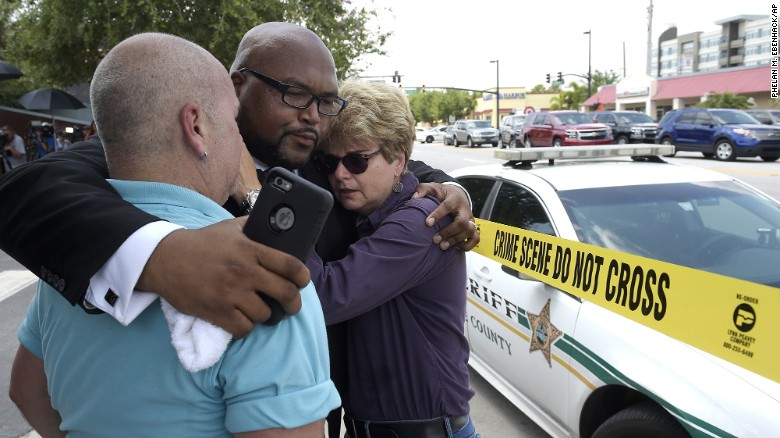 Church pastor Kelvin Cobaris hugs Orlando City Commissioner Patty Sheehan and Terry DeCarlo, executive director of the LGBT Center of Central Florida, after a shooting at the Pulse nightclub killed at least 50 people and injured at least 53 on Sunday, June 12. Orlando police said they shot and killed the gunman.
