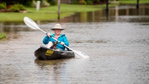 Jennifer Bernard and her dog Shelby travel by kayak down the flooded streets of Youngsville, Louisiana, on Sunday, August 14.
