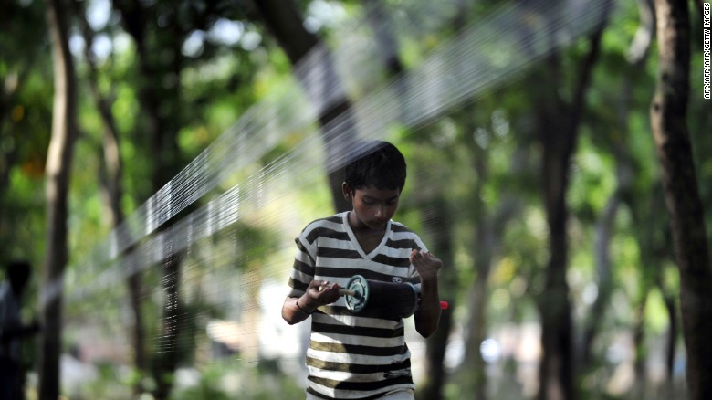 "An Indian youth prepares ""manja,"" a strong string used to fly kites, in Allahabad on April 9, 2013."
