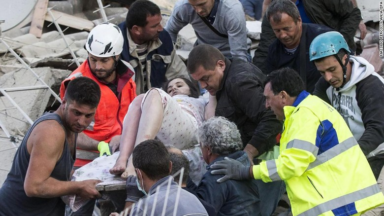 epaselect epa05508238 An injured woman (C) is carried by rescuers amid the rubble of collapsed buildings in Amatrice, central Italy, 24 August 2016, following a 6.2 magnitude earthquake, according to the United States Geological Survey (USGS), that struck at around 3:30 am local time (1:30 am GMT). The quake was felt across a broad section of central Italy, including the capital Rome where people in homes in the historic center felt a long swaying followed by aftershocks. According to reports at least 21 people died in the quake, 11 in Lazio and 10 in Marche regions.  EPA/MASSIMO PERCOSSI