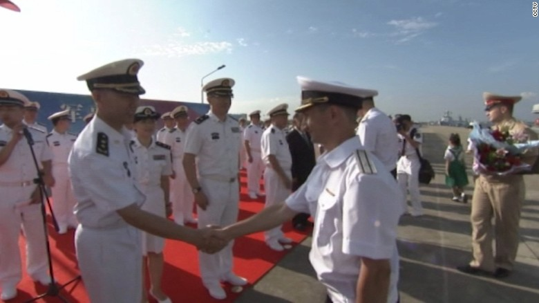 Russian and Chinese officers greet each other at the beginning of eight days of military exercises.