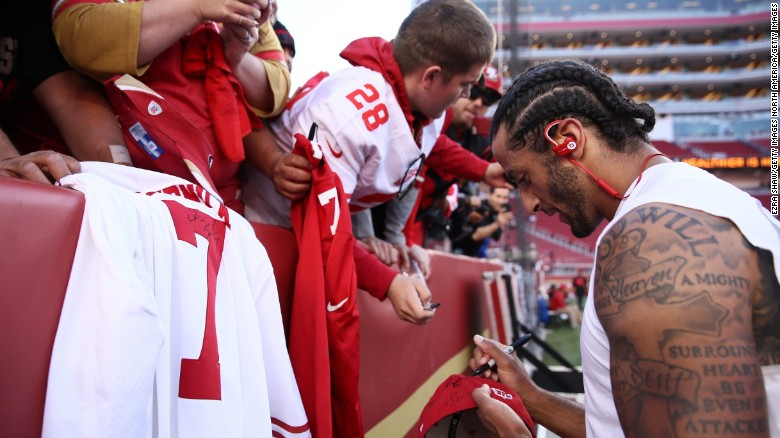 Kaepernick signs an autograph for a fan prior to playing the Los Angeles Rams in their NFL game at Levi's Stadium.
