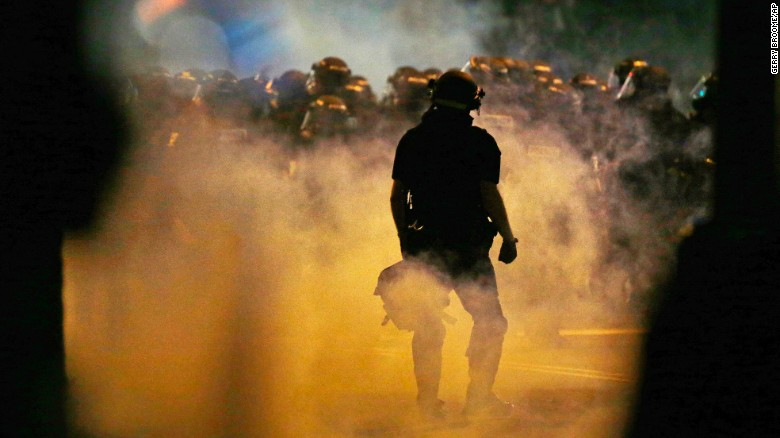 Police fire teargas as protestors converge on downtown following Tuesday's police shooting of Keith Lamont Scott in Charlotte, N.C., Wednesday, Sept. 21, 2016. Protesters have rushed police in riot gear at a downtown Charlotte hotel and officers have fired tear gas to disperse the crowd. At least one person was injured in the confrontation, though it wasn't immediately clear how. Firefighters rushed in to pull the man to a waiting ambulance.(AP Photo/Gerry Broome)