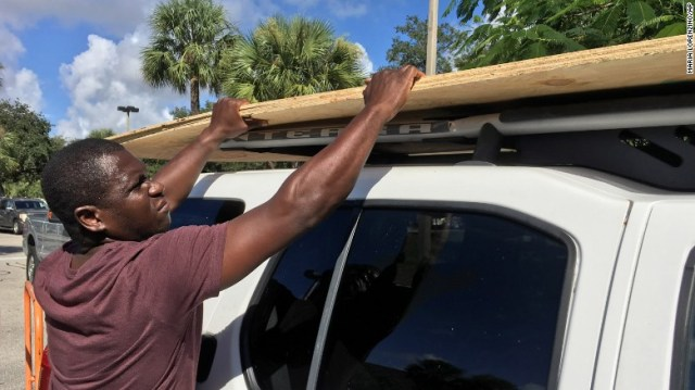 Texroy Spence, of Deerfield Beach, Florida, loads plywood onto his car at the Home Depot in Deerfield Beach, Florida on Tuesday, October 4, 2016.