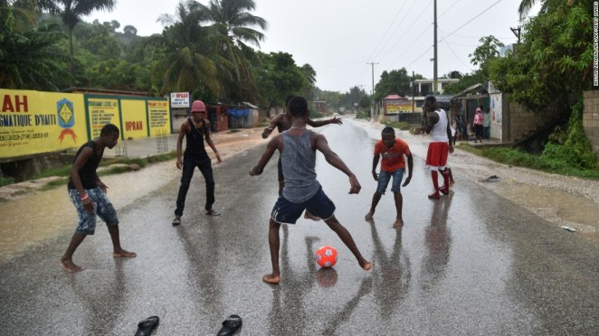 A group of young men play football in the rain on the roat to Leogane, as the hurricane passes.