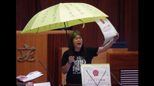 Leung Kwok-hung, holds a yellow umbrella and an oversized mock copy of the proposed anti-subversion legislation as she takes oath.