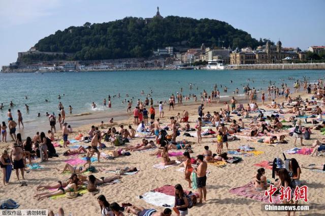 """西班牙海滩游人扎堆 """"玉体横陈""""晒日光浴"""