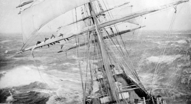 Close up of the mast of a large iron or steel sailing ship. Four men are wrapping up the sails high above the main deck. The ship is sailing in rough seas and there are large waves surrounding the ship.