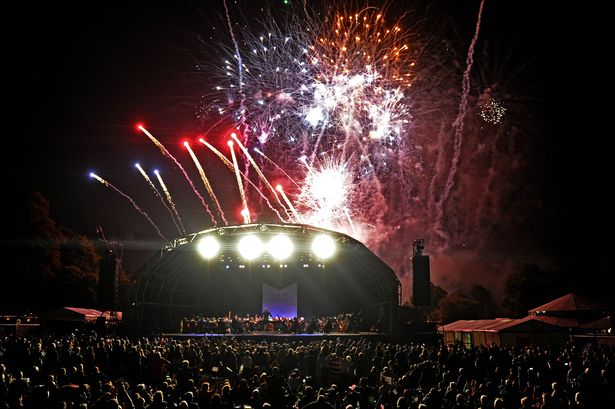 Liverpool International Music Festival opening night at Sefton Park with Liverpool Philharmonic performing on stage as fireworks light up the night sky
