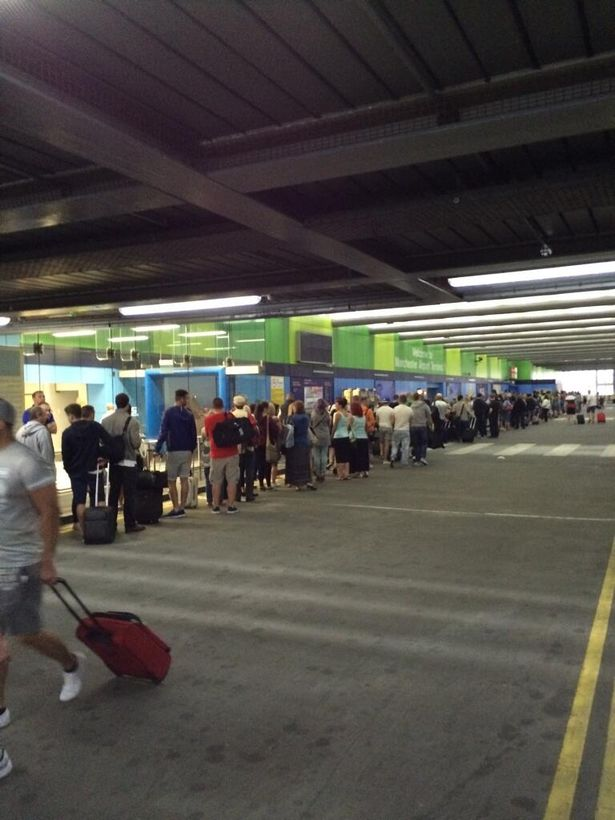 Passengers queue outside the terminal at Manchester Airport