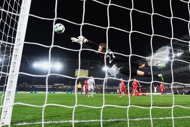 Simon Mignolet makes a save from Gylfi Sigurdsson