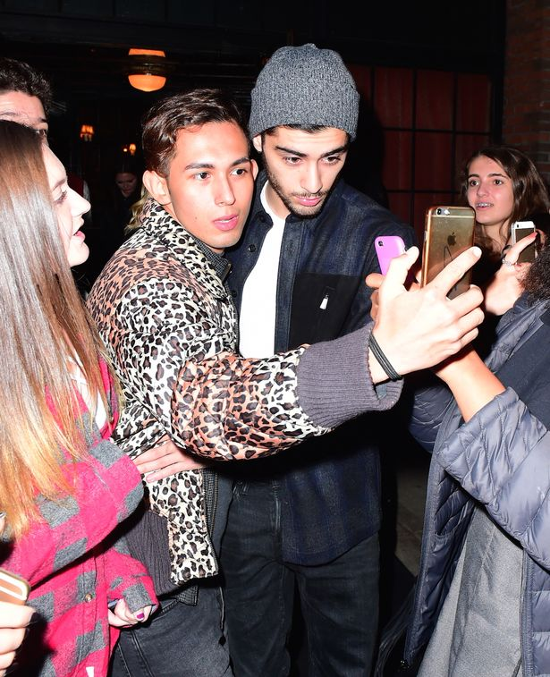 Zayn Malik squeezes past the fans in downtown Manhattan