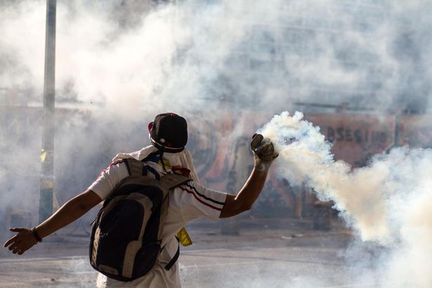 A demonstrator throws an object during a protest in Altamira, in the municipality of Chacao, east of Caracas, Venezuela, on March 16, 2014.