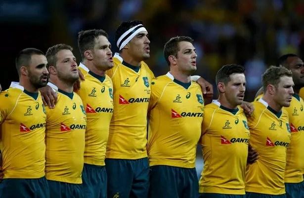 Australian team mates listen to national anthems before their match