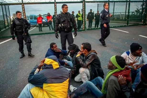 gendarmes franceses se enfrentan los migrantes en el sitio Eurotunnel cerca de los muelles de embarque en Coquelles cerca de Calais