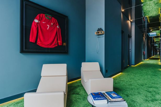 A corridor within the hotel with a Cristiano Ronaldo Portugal framed shirt, mirrored ceilings and a grass themed floor