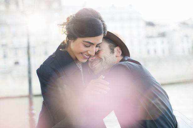 Couple hugging along Seine River, Paris, France