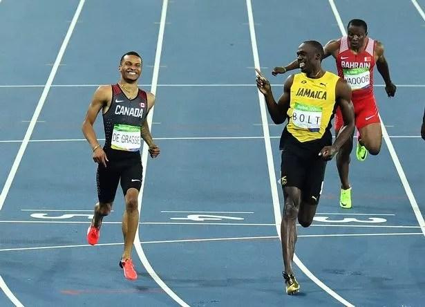Jamaica's Usain Bolt (R) shares a laugh with de Canada's Andre De Grasse