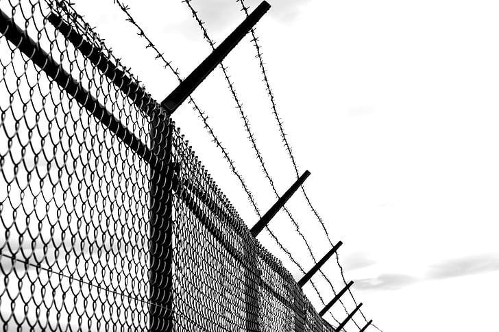 Royalty-Free photo: Cyclone wire fence with barb wire