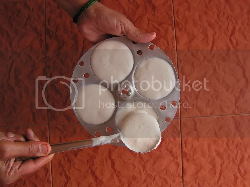 idli batter being filled in idli maker