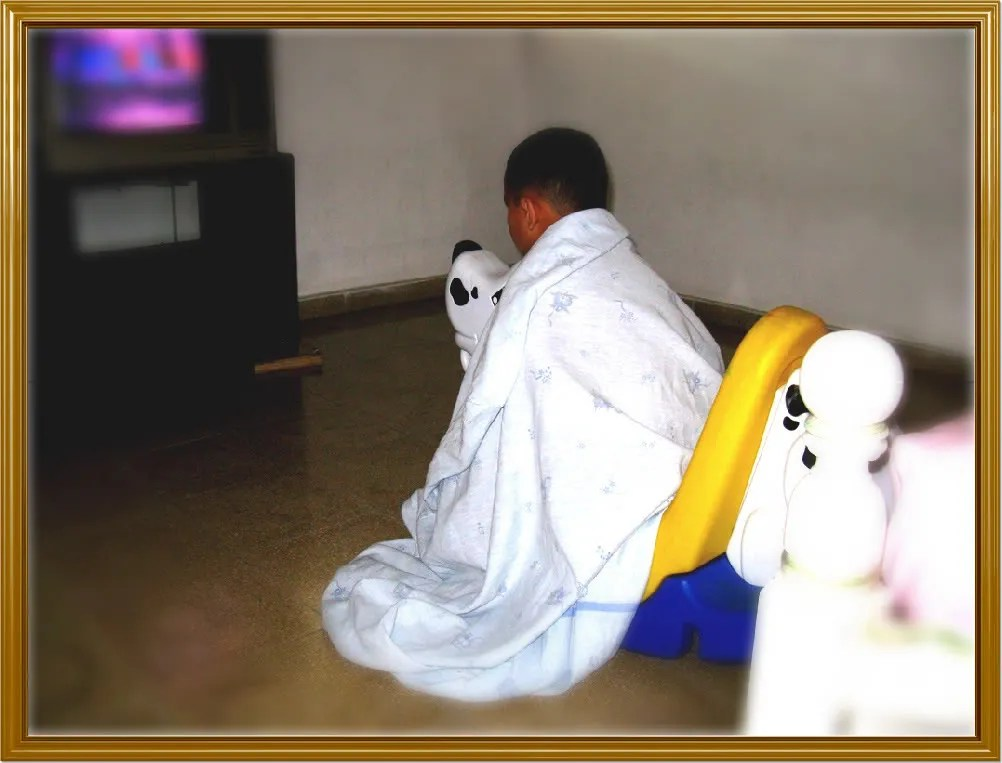 Photograph of Abdiel rocking on a plastic dog, wrapped up in a sheet and with his eyes glued to the screen of the TV set.