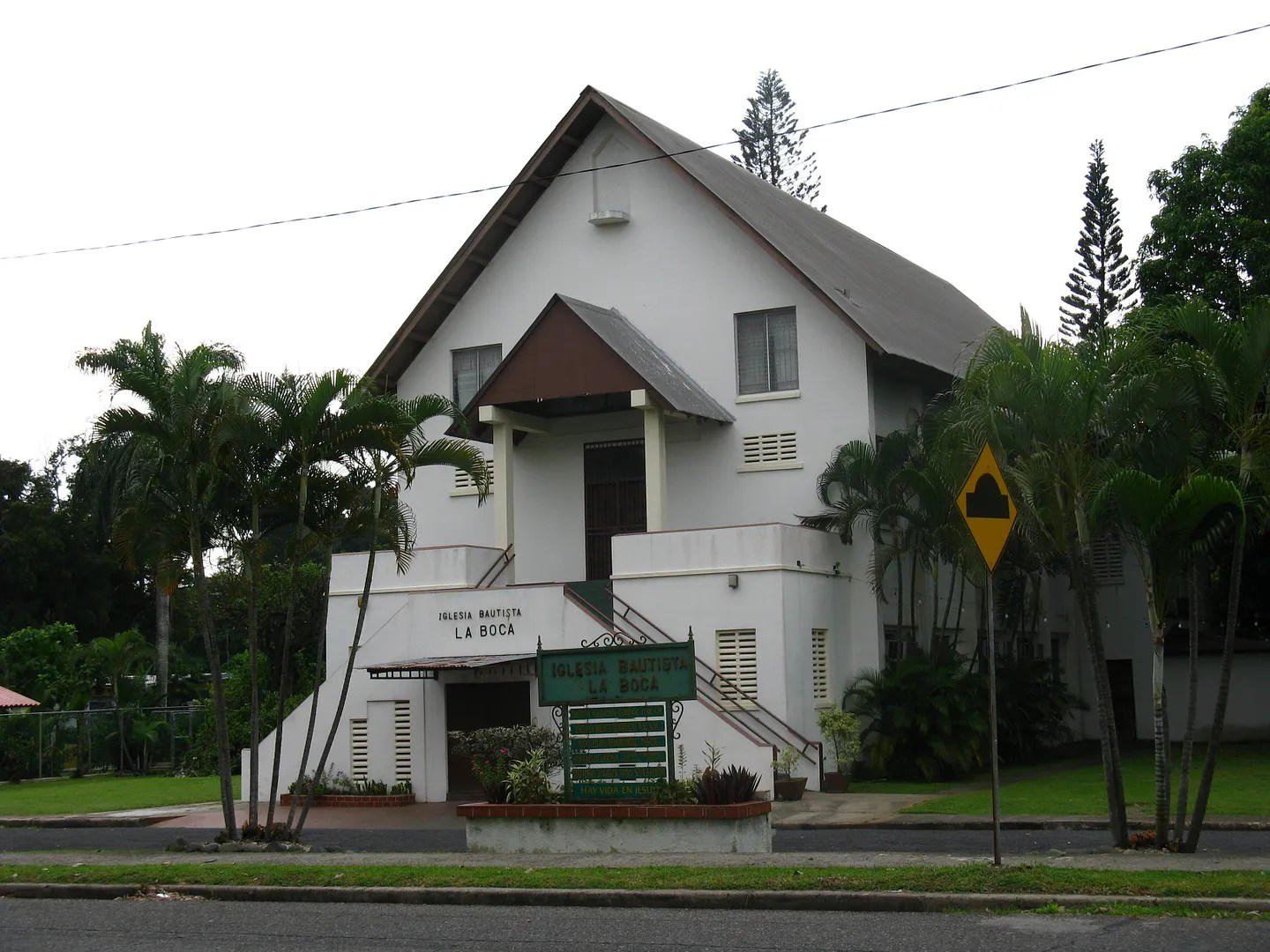 Photograph of the La Boca Baptist Church located at the entrance of the Panama Canal 3 miles downstream.  Notice the tall elegant pine trees in the background.  (Credit:  Omar Upegui R.)