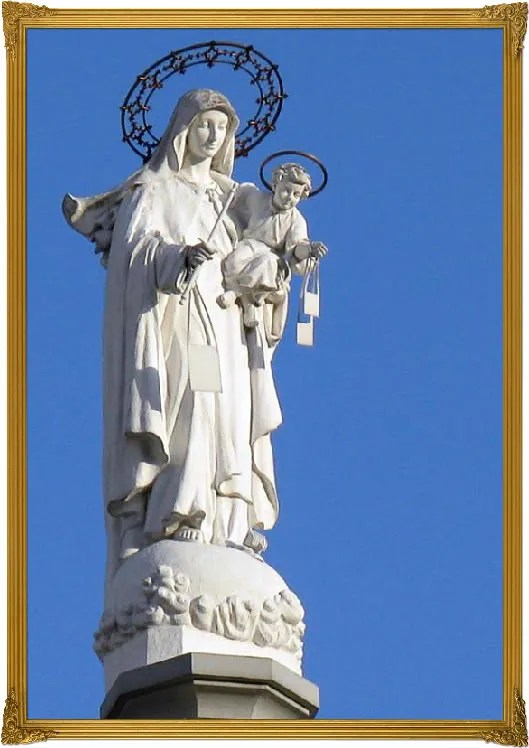 View of the statue of Virgin Mary and Baby Jesus.  From the ground its very difficult to admire the great piece of religious art.
