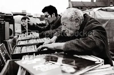 Old man digging through crate of vinyls