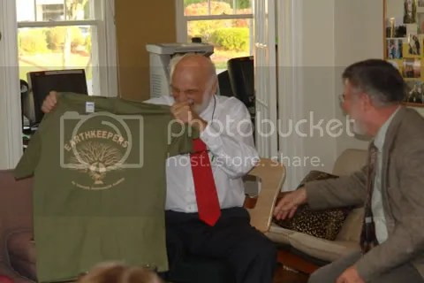At the Northern Michigan University Lutheran Campus Ministry house, Theologian Dr. Walter Brueggemann shows an Earth Keeper Shirt he was given while sharing a laugh with Marquette Baha'i Spiritual Assembly leader Dr. Rodney Clarken, one of the 10 Earth Keeper Initiative faith communities.