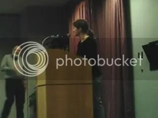 Northern Michigan University Earth Keeper (NMU EK) Student Team Project Director Jennifer Simula turns podium over to Professor Don Dreisbach of NMU Dept. of Philosophy who introduced biblical Scholar Walter Brueggemann