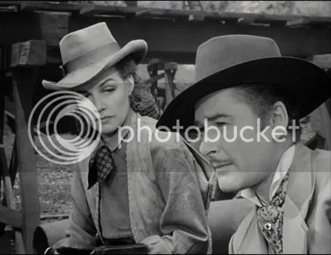 Ann Sheridan casts a distrustful glance at Errol Flynn.