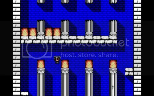 A room with white bricks. Four pillars, each with a flame on top. Between the leftmost two jumps a pixelatred woman clad in leather. Above is another floor with another four pillars, broken in half. A pair of flames is in front of each of the two leftmost pillars.