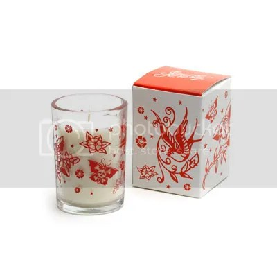 cherry red tattoo designs swirl around a good sized white candle (which