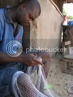 Fisherman repairs nets