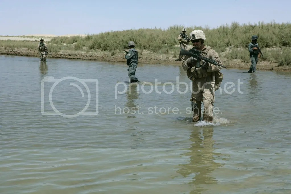 Afghan National Police officers and U.S. Marines cross a river during a security patrol in the Garmsir district of the Helmand province of Afghanistan Sept. 12, 2009.