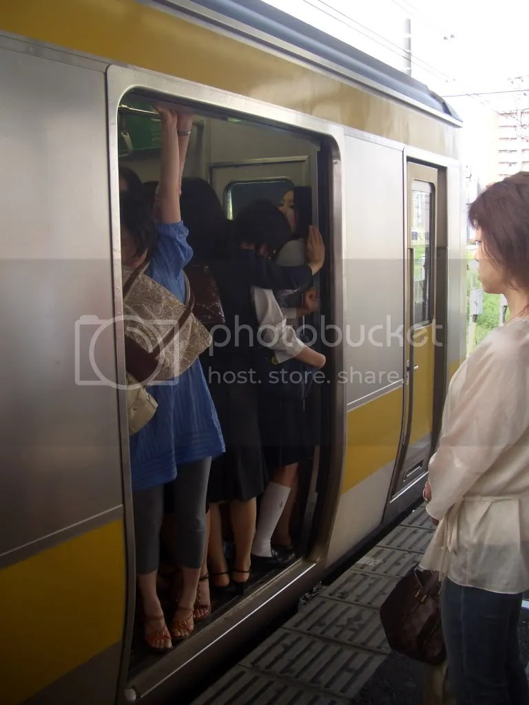 People brace themselves to avoid falling out of the rather overstuffed train