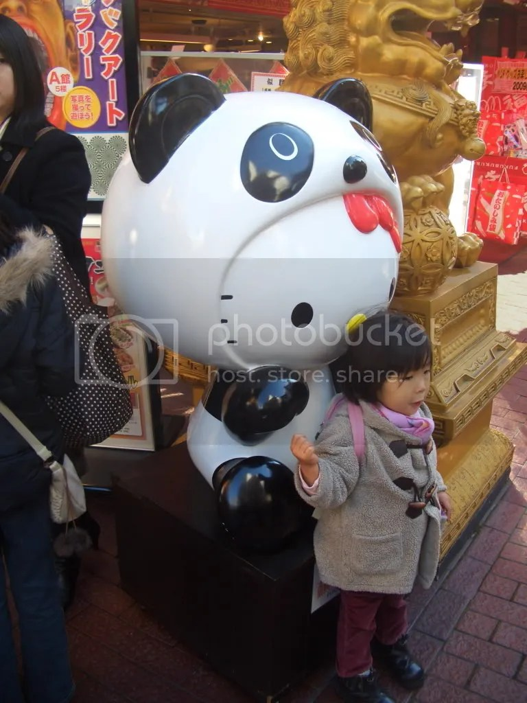 Culture Clash. A child poses in front of a statue of Hello Kitty in a Panda suit