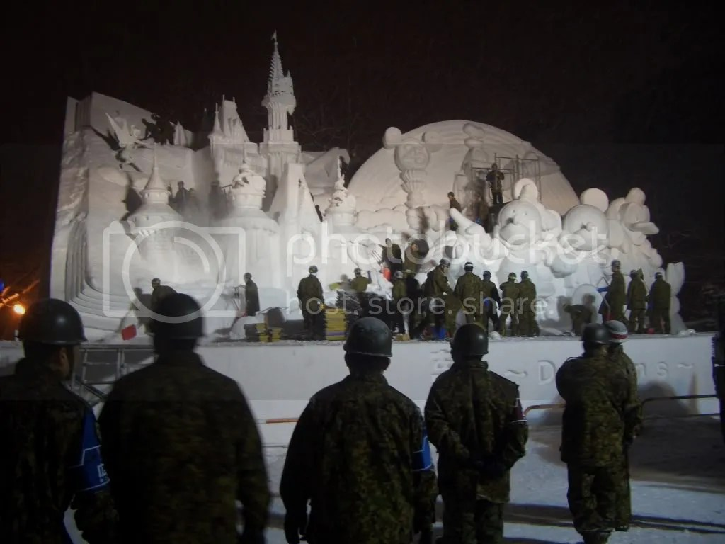 The Japan Self Defense Forces helps to build and maintain the sculptures. Here they are touching up the Disney themed sculpture