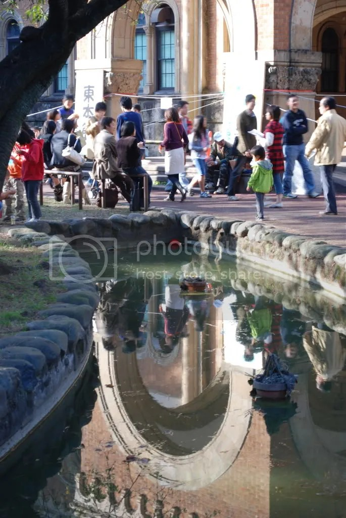 Reflections in the water of people visting the campus for the festival.