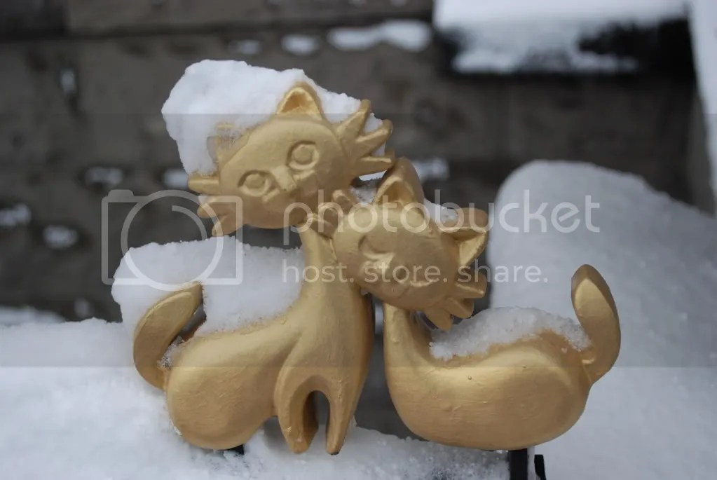 Balustrade encircling the building. Cute kitty cats covered in snow.