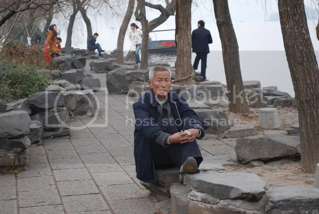 A man relaxes next to the West Lake