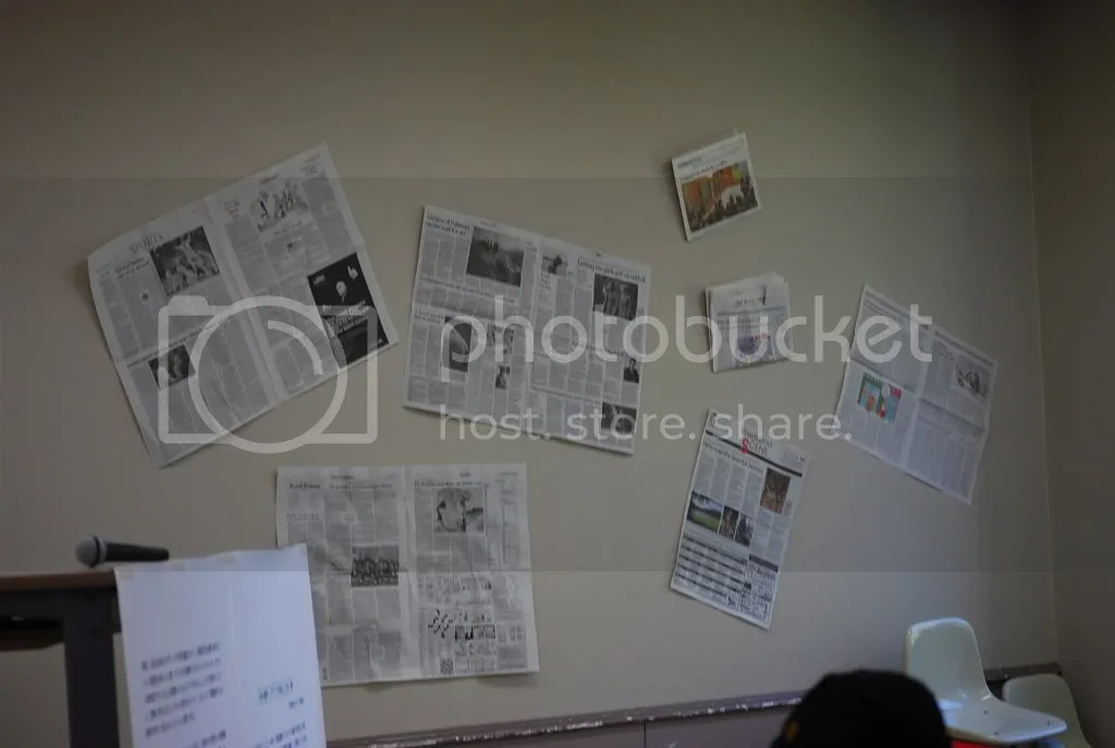 Newspapers cover a wall in a room where a club has an exhibition about news media