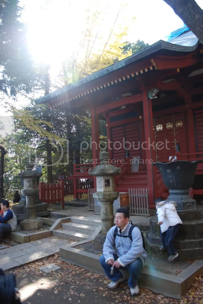 A man takes a break in front of a shrine