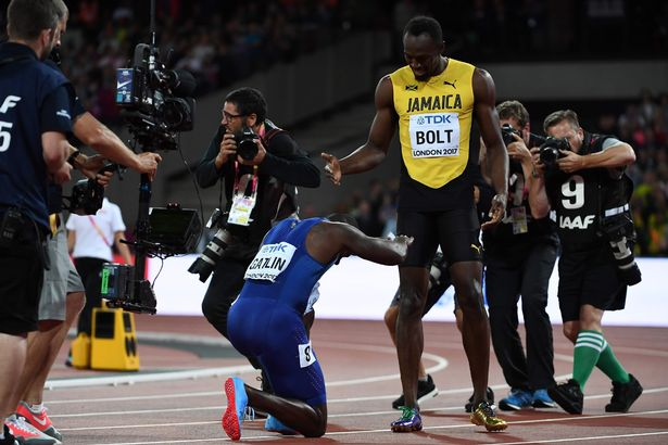 US athlete Justin Gatlin (L) bends down to Jamaica's Usain Bolt after the final of the men's 100m