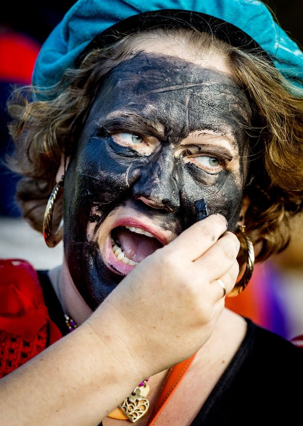 A woman paints her face black as she dresses up as Zwarte Piet (Black Pete) during a demonstration in favor of the character, Saint-Nicholas' helper, at the Malieveld, in The Hague, The Netherlands,