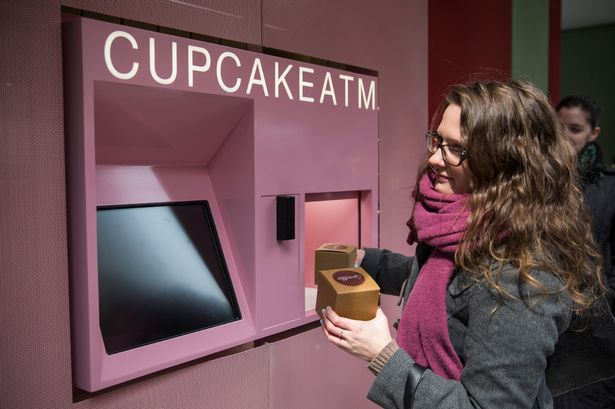 """A woman takes her order of cupcakes after using a """"Cupcake ATM"""" created by Sprinkles bakery on March 25, 2014 in New York City"""