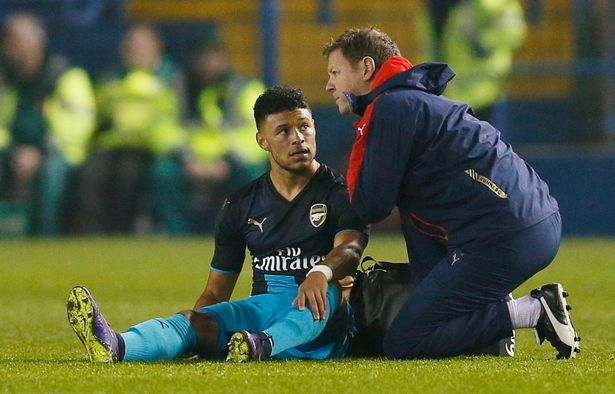 Alex Oxlade Chamberlain receives treatment after sustaining an injury before being substituted
