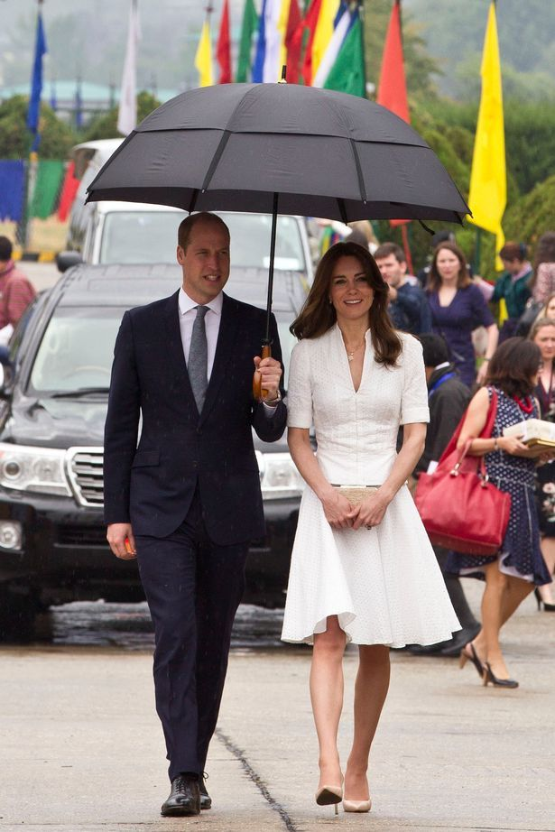 William held an umbrella for wife Kate as they made a damp departure from Bhutan
