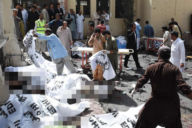 Pakistani volunteers cover the bodies of victims after a bomb explosion at a government hospital premises in Quetta