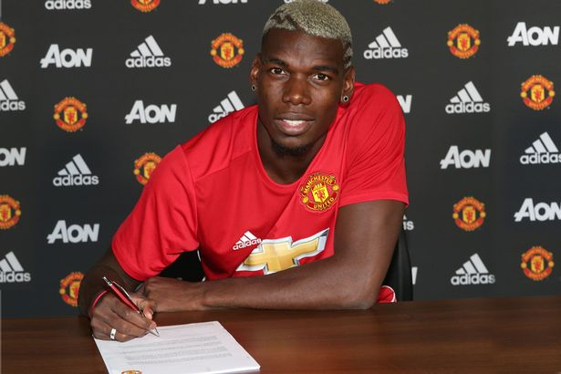 Paul Pogba poses after signing for Manchester United